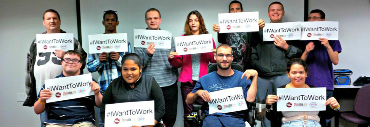 Group holds up I want to work signs